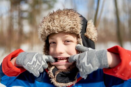 Portrait of a smiling boy being silly and pulling a face in fresh snow during wintertime Reklamní fotografie