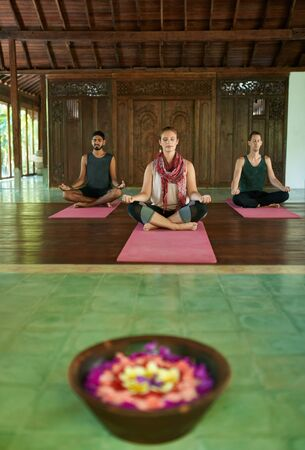 Three diverse real people sitting in lotus pose meditating together in a traditional temple in Bali Indonesia Фото со стока - 134507770