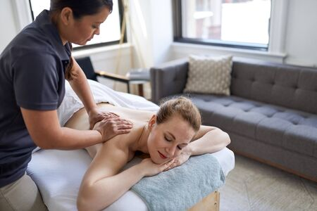 Chinese woman massage therapist giving a treatment to an attract