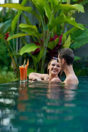 Two real young healthy people on vacation drinking in resort poo
