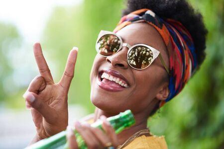 Jolie jeune femme afro-américaine prenant un verre en écoutant Banque d'images