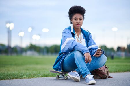Attractive young african american woman skaterboarder sittting o