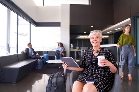 Professional woman sitting in airport wearing trendy dress smili