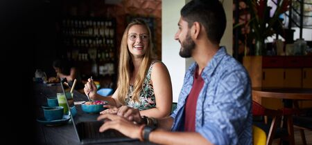 Couple smiling together sitting at table and discussinga small b Stock Photo