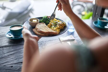 Closeup shot of delicious brunch plate with multi-grain bread, butter, fried greens, egg, organic coffee being eaten with fork on rustic table near window