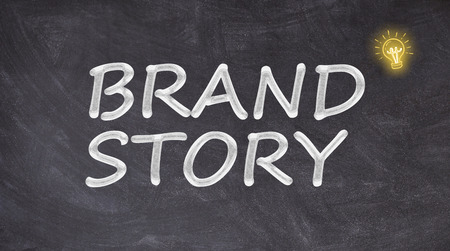 Brand story written on blackboard with light bulb Stok Fotoğraf
