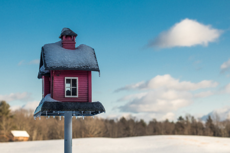 Red wooden birdfeeder under the snow