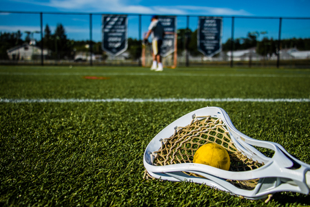 A white lacrosse net holding a yellow ball is laying on the grass