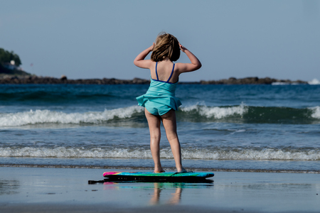 A little girl in blue swimming  suit is surfing at the beach