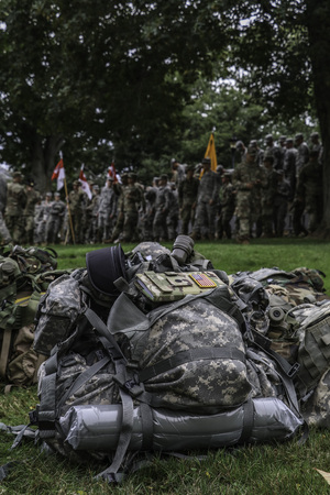 Soldiers backpack in foreground of standing soldiers