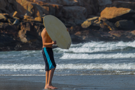 Young man hiding his face with surfing board at the beach