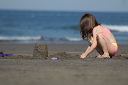 A little girl in pink swimming  suit is playing with sand at the beach