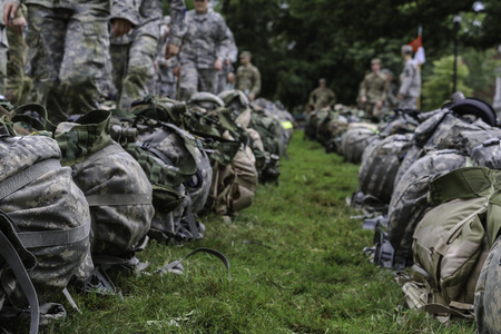 Soldiers marching by backpacks on grass