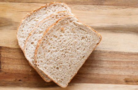 Sliced bread on wooden background from above.