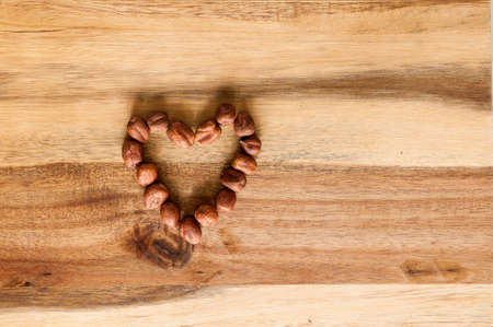 Heart made of hazelnuts on wooden background.