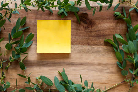 Single sticky notes  on a wooden background surrounded by a leafy green frame.