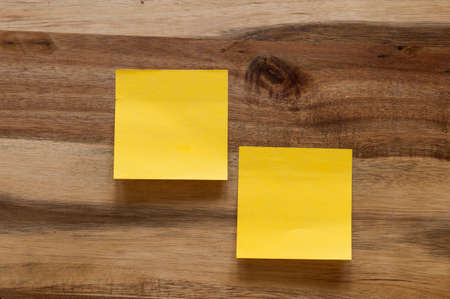 Two stickynote on a wooden background.