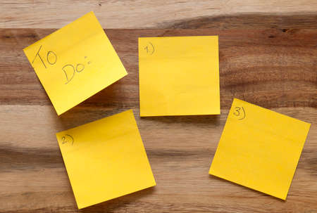 Five sticky notes numbered one to five on a wooden background.