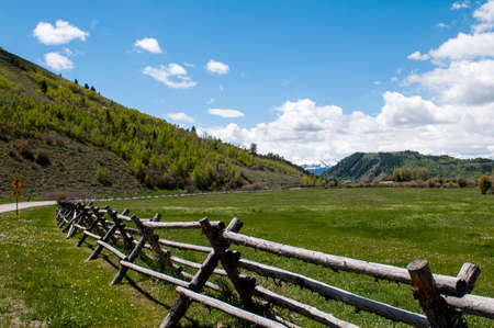 Country road and fence in Jackson Hole, Wyoming with snowcapped mountains in the background