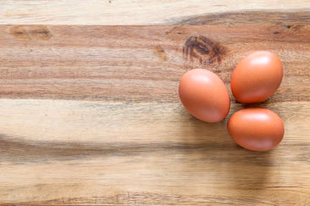 Three eggs on a wooden background