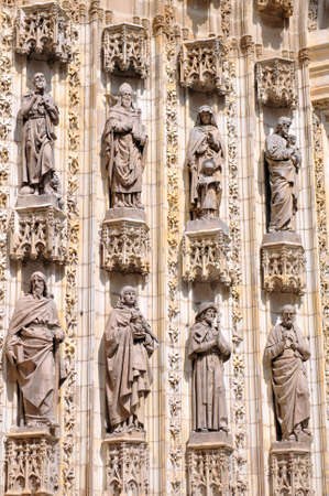 Statues of saints carved in stone, detail of exterior in the Cathedral of Seville, Andalusia, Spain. Stock Photo