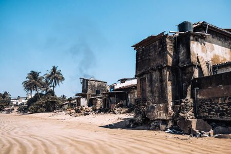 Fire damaged buildings in the middle of popular touristic beach in Sri Lanka. Polluted and damaged place near surfing beach.