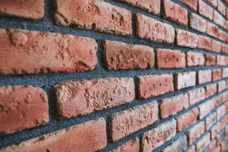 Side angle of a red brick wall. Close up view of cracked weathered cemented brickwork material. Modern interior design, unique perspective. Loft like room style at home. Rusty facade architecture. Stock Photo