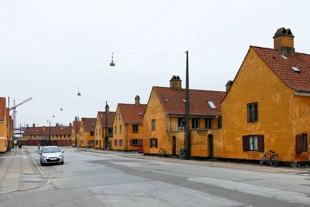 Single car on an empty deserted street in a European popular capital Copenhagen, Denmark. Bright orange painted beautiful buildings. Hygge houses without all people at home. Colorful city landscape.
