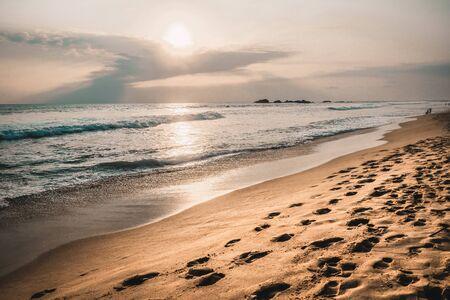 Popular touristic place Mirissa beach in Sri Lanka empty on sunset; sunset photo with calm colors; coastline view in southern Sri Lanka.