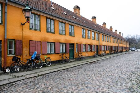 Empty deserted street in a European popular capital Copenhagen, Denmark. Bright orange painted beautiful buildings. Hygge houses without people. Colorful city landscape with nobody around.