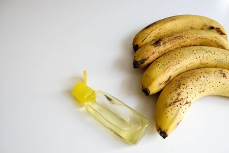 Close up view of a yellow bananas row and a bottle of hand sanitizer on a white desk. Healthy diet for good immunity and covid-19 virus spreading prevention. Antibacterial germ killing gel at home.