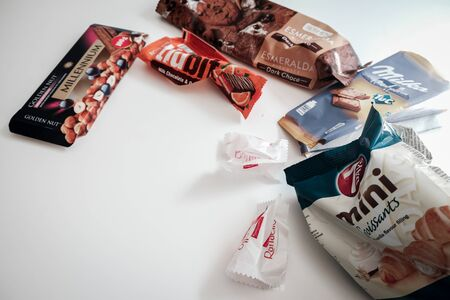 Lviv / Ukraine - April 2020: Assorted candy, cookie and chocolate wrappers left on a white table. Delicious sweets full of sugar that leads to health issues and overweight. Binge eating in isolation.