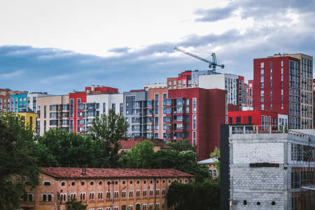 Top view of construction site in modern city. Colorful buildings in residential area. Beautiful cityscape architecture in Eastern Europe. House rooftops in sleeping quarters downtown.