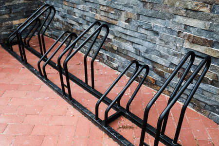 Empty black bicycle rack during pandemic. No people out on parking, sitting at home in isolation. Using bike for transportation to avoid air pollution. Alternative transport for carbon monoxide issue.