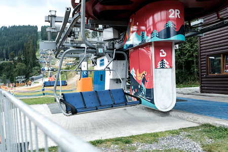 Bukovel, Ukraine - July 2020: Empty ski lift or chairlift at Ukrainian resort Bukovel in summertime. Less tourists during pandemic isolation. Local travel, spending weekend in Carpathian mountains. 新闻类图片
