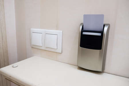 Closeup view of a security key card that controls power in a hotel room. Inserting cardkey for access and safety. Modern identification on vacation. Energy + electricity switch card holder on a wall. 免版税图像 - 158005961