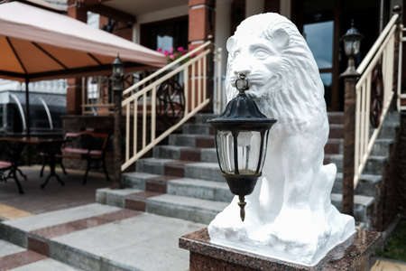 White lion statue holding an old lantern in front of a hotel or restaurant facade. Stairs in the background. Hospitality concept. Sightseeing in eastern Ukraine. Lviv, historical old city of lions.