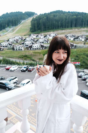 Beautiful girl in white hotel bathrobe drinking hot tea or coffee on a balcony. Nature and nice view outside. Quiet weekend getaway in the mountains. Holding a cup and smiling at a beautiful morning.