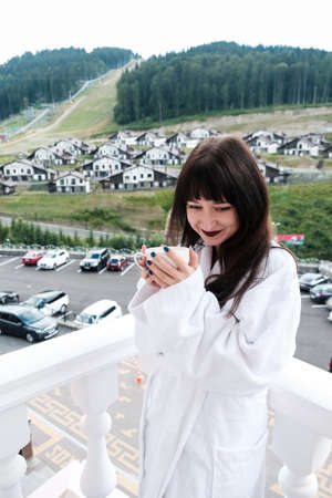 Beautiful shy girl in white hotel bathrobe drinking hot coffee on a balcony. Nature and nice view outside. Quiet weekend getaway in the mountains. Holding a cup and smiling at a beautiful morning.