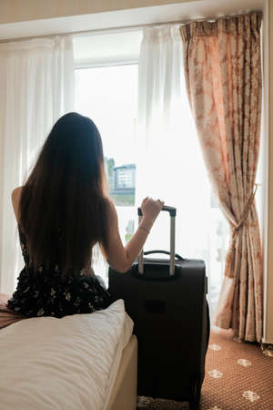 Sad young woman with luggage ready to leave the hotel room. Last day of vacation. Time to go back home. Short trip during isolation, restricted travel. Leaving finished weekend getaway spa retreat. 免版税图像
