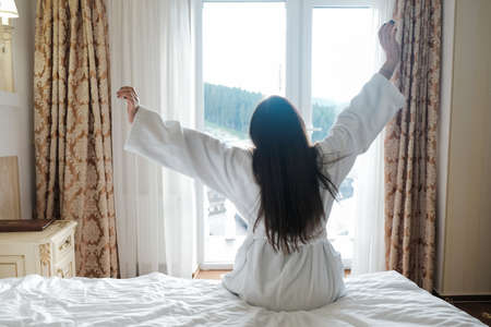 Young brunette girl stretching in hotel room bed in the morning. Waking up full of energy on vacation, arms raised and fully awake. Happy and lazy early day. Female sitting in bathrobe on a retreat.