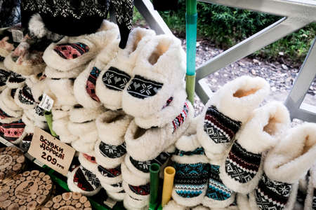 Bukovel, Ukraine - July 2020: Selling warm cozy woolen shoes for home at a Ukrainian fair. Local craftsmanship for tourists. Present or gift ideas for winter or fall. Traditional souvenir from Ukraine