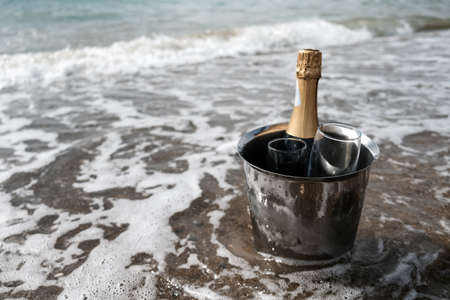 Ice bucket with champagne bottle and glasses on a beach surrounded by sea. Ocean waves chilling drinks, luxury vacation for two. Anniversary day, romantic holiday or honeymoon together. Tourist couple