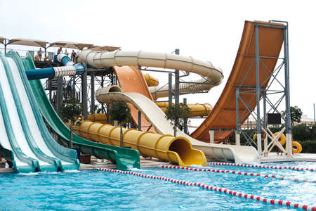 Belek, Turkey - October 2020: Colorful slide variety and turquoise swimming pool at an all inclusive resort. Water reflection in empty kids aqua park during pandemic isolation. Nobody has fun in water 新闻类图片