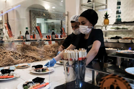 Belek, Turkey - October 2020: Staff serving delicious Japanese food in all inclusive resort. Sushi for lunch for tourists at a luxury vacation place. Waiters in face masks and gloves during pandemic.