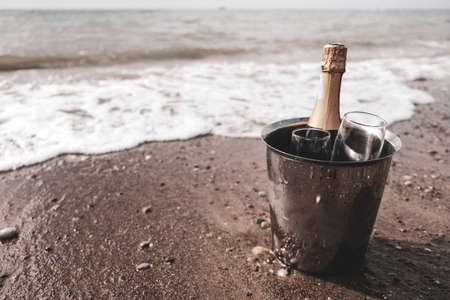 Ice bucket with champagne bottle and glasses on a beach surrounded by sea. Ocean waves chilling drinks, luxury vacation for two. Anniversary day, romantic holiday or honeymoon together. Sepia colored.