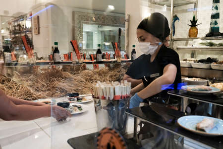 Belek, Turkey - October 2020: Hotel staff serving Japanese food in an all inclusive resort in Antalya. Sushi for lunch for tourists at a luxury vacation place. Waiters in face mask during pandemic.