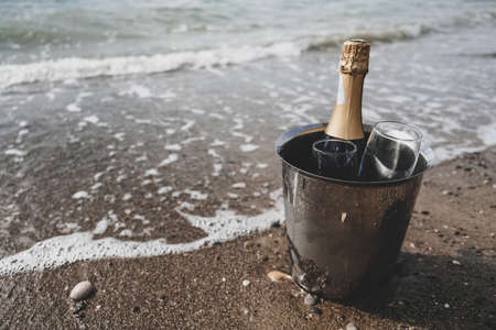 Ocean waves chilling drinks for tourists, luxury vacation for two. Ice bucket with champagne bottle and glasses on a beach surrounded by sea. Anniversary day, romantic holiday or honeymoon together.