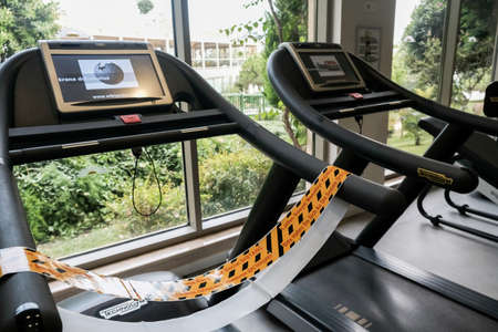 Belek, Turkey - October 2020: Safety measures to prevent coronavirus spreading. Yellow tape on a restricted treadmill for social distancing. Stay active but keep safe during run and cardio exercises.