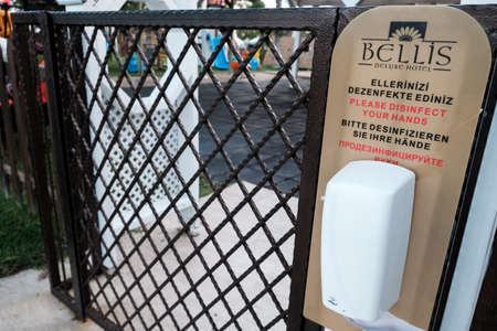 Belek, Turkey - October 2020: Sanitizer device hanging on a fence near kindergarten club entrance at a hotel. Safety measures in all-inclusive resort to prevent coronavirus spread during pandemic. 新闻类图片
